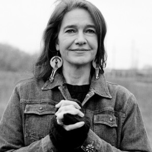 Louise Erdrich in black and white from the chest up, posing outdoors. She wears a denim jacket, a black jumper and round earrings, and her hands are joined in front of her. She smiles as she looks past the photographer into the distance. There is a field behind her, out of focus.