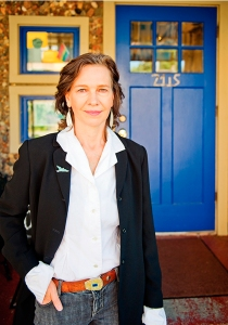 Author Louise Erdrich, in jeans, a white blouse and a black jacket, poses by a blue door marked 2115.