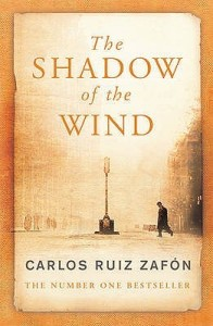 The cover of The Shadow of the Wind: a street is represented in the yellowish-brown shades of old photographs. There is a lampost in the centre of the image, towards which a man walks from the right.
