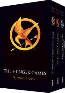 The boxset of The Hunger Games. The box is solid black, with a golden mockingjay emblazoned on the front. It flies through a golden circle holding a golden arrow in its beak. The box is placed at an angle, so you can see the spine of the three individual books on the right. There is a variation of the mockingjay at the top of each spine: the golden one is repeated on The Hunger Games; Catching Fire sports a red one, while Mockingjay has a silver blue one.