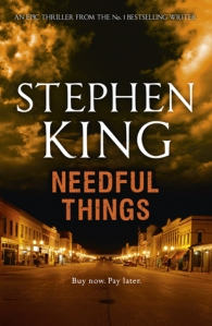 The cover of the book Needful Things: a deserted street at night, with shop fronts lit up on each side. Dark cloud hover above.