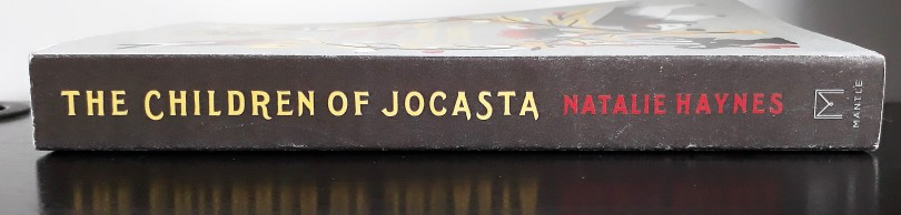 A photo of the spine of a proof copy of The Children of Jocasta. It is black, with the title in yellow and the author's name in red. The book lies on a black desk.