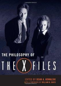 "The cover of The Philosophy of The X-Files. Actors David Duchovny and Gillian Anderson are photographed in black and white and from above. They are in their characters' business clothes and look up at the camera. The title is at their feet, centered left and broken into two lines. ""The Philosophy of"" is written in a small white font, while ""The X-Files"" logo underneath is typed in a much bigger font. The ""X"" is in a black, red-rimmed circle, for emphasis. At the very bottom is a black banner, indicating the author and foreword author's names, in the same red that circles the letter X above."