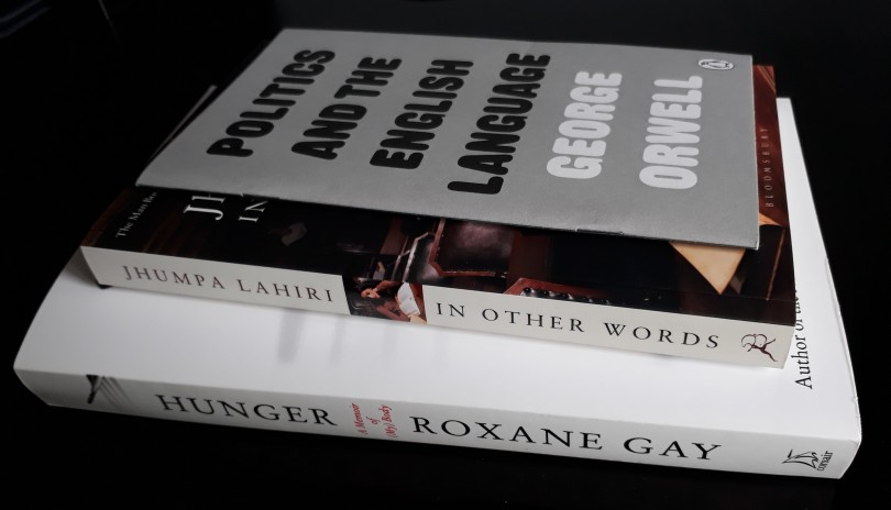 Roxane Gay's Hunger, Jhumpa Lahiri's In Other Words and George Orwell's Politics and the English Language stacked in a pile on a black desk.